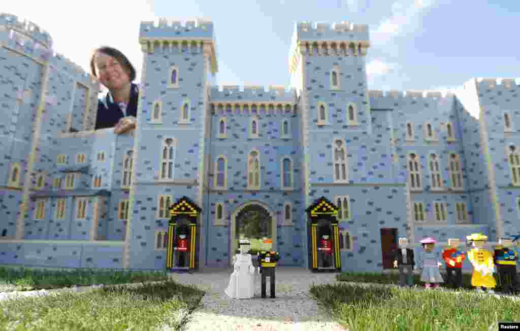 Head model maker, Paula Laughton, poses for a photograph with a LEGO Windsor Castle replete with a royal wedding scene between Britain's Prince Harry and Meghan Markle, in Windsor, England.