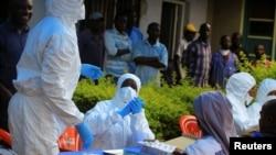 Abategetsi ba Kongo hamwe n'aba OMS imbere yo gutanguza isekeza ry'urucanco rwa Ebola, hafi y'intara ya Beni, mu buraruko bwa Kivu, DRC, Italiki 08/08/2018.