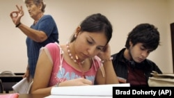 University of Texas-Southmost College students, Jessica Vargas, center, and Patrick Flores, right, work on a writing assignment.