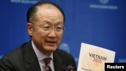 """Chủ tịch Ngân hàng Thế giới Jim Yong Kim cầm bản báo cáo """"Việt Nam 2035: Hướng tới Thịnh vượng, Sáng tạo, Công bằng và Dân chủ"""" trong cuộc họp báo tại Hà Nội, ngày 23/2/2016."""