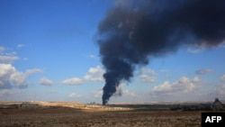 FILE - Smoke billows from a weapons depot allegedly belonging to rebel fighters during an operation by Syrian regime forces to take control of the Al-Maleh farms, west of the Handarat hill which is located just north of Aleppo, on Dec. 15, 2014.
