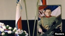 A portrait of Arkan, real name Zeljko Raznatovic, is displayed next to a couple of Serbian flags and a wreath during his commemoration service in Belgrade. Photo: Goran Tomasevic/Reuters.