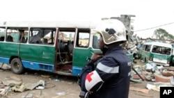 Un policier traverse une cour jonchée de carcasses de véhicules et de débris, après l'explosion du 4 mars