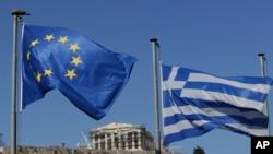 Bendera Uni Eropa dan bendera Yunani berkibar di Acropolis, Athena (foto: dok). Parlemen Yunani akan melakukan voting atas RUU paket dana talangan hari Kamis (13/8).