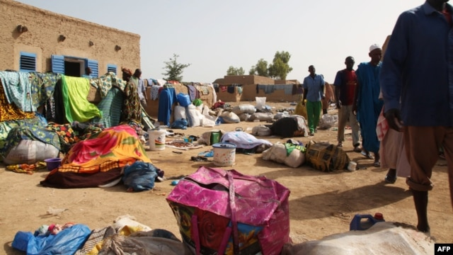 People who survived after the sinking of a river boat walk near their belongings on the banks of the Niger river, Oct. 13, 2013 in Koubi.