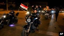 Cư dân chạy xe máy ăn mừng sau khi lệnh giới nghiêm ban đêm ở Baghdad được dỡ bỏ, ngày 7/2/2015.