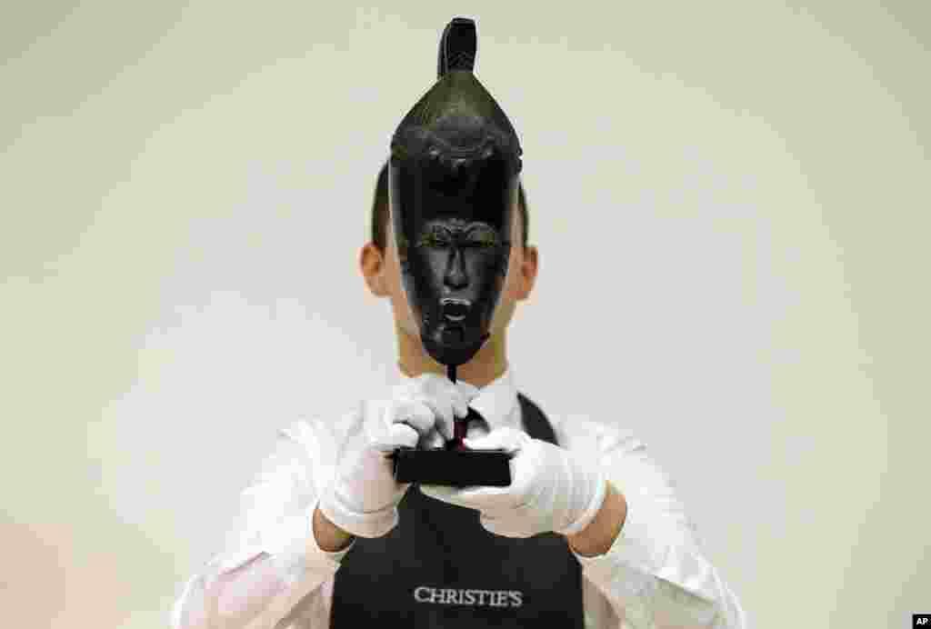 Funcionário da leiloeira Christie's mostra uma máscara da Costa do Marfim que deverá atingir um valor de mais de meio milhão de dólares.