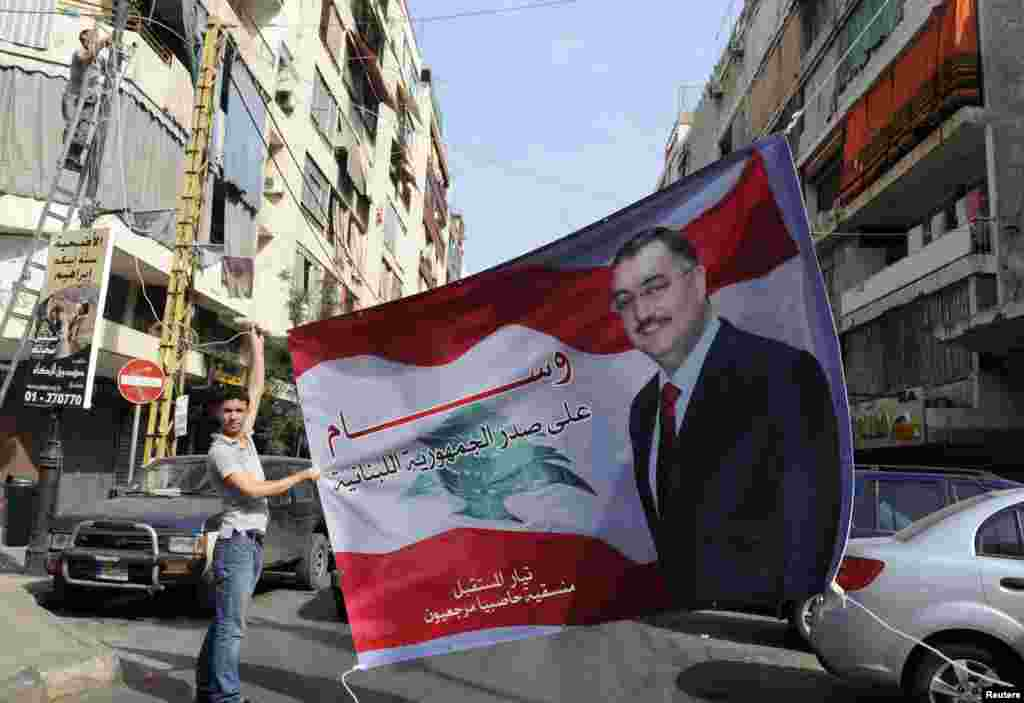A Sunni Muslim man hangs up a poster with an image of senior intelligence official Wissam al-Hassan, in the Tariq al-Jadideh district in Beirut, October 20, 2012.