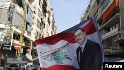 Một người Hồi giáo Sunni giương cao hình ông Wissam al-Hassan ở quận Tariq al-Jadideh, tại Beirut, ngày 20/10/2012.