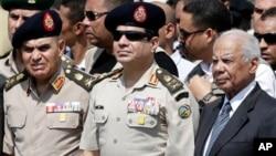 Menhan Mesir, Abdel-Fattah el-Sissi (tengah) bersama Perdana Menteru Hazem el-Beblawi (kanan) pada upacara pemakaman Kepala Polisi Giza, Nabil Farrag, di Kairo (foto: dok).