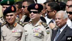 FILE - Egyptian Defense Minister Gen. Abdel-Fattah el-Sissi, center, Egyptian Prime Minister Hazem el-Beblawi, right, at funeral of Giza Police General Nabil Farrag, Cairo, Egypt.