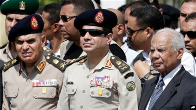 FILE - Egyptian Defense Minister Gen. Abdel-Fattah el-Sissi, center, Egyptian Prime Minister Hazem el-Beblawi, right, at funeral of Giza Police General Nabil Farrag, Cairo, Egypt.