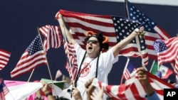 FILE — A man waves an American flag during a during a rally in Atlanta, Georgia.