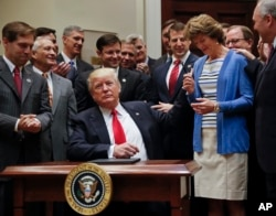 President Donald Trump, gives the pen he used to sign an Executive Order to Sen. Lisa Murkowski, R-Alaska, right, in Washington, April 28, 2017. The order directs the Interior Department to begin review of restrictive drilling policies for the outer-continental shelf.
