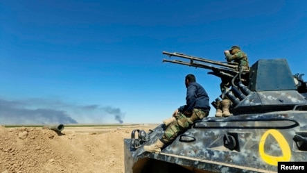 Shi'ite fighters sit on a military vehicle in Al Hadidiya, south of Tikrit, en route to the Islamic State-controlled al-Alam town, where they are preparing to launch an offensive on Saturday, March 7, 2015.