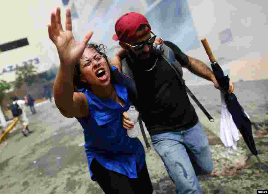 A woman affected by tear gas is assisted during a May Day protest against austerity measures, in San Juan, Puerto Rico, May 1, 2018.
