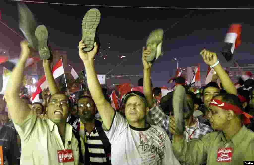 Người biểu tình chống tổng thống Mohamed Morsi giơ giày biểu thị thái độ khinh miệt sau khi ông Morsi phát biểu trực tiếp trên truyền hình tại Quảng trưởng Tahrir ở Cairo, 3 tháng 7, 2013.