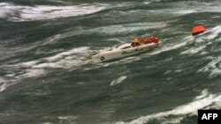 """FILE - The injured crew of demasted Australian yacht """"Stand Aside"""" await rescue by helicopter as they tow a life-raft in Bass Strait during the Sydney-to-Hobart ocean race, Dec. 27, 1998."""