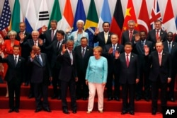 U.S. President Barack Obama, front row third from left, Chinese President Xi Jinping, second from right, and other leaders wave as they pose for a group photo session for the G-20 Summit held at the Hangzhou International Expo Center in Hangzhou.