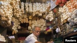 A vendor exchanges money with a customer at a shop selling garlic, onions and potatoes at a wholesale market in Mumbai.