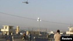 Petugas keamanan Afghanistan melakukan penjagaan ketat, saat helikopter NATO melintasi lokasi kejadian ledakan bom bunuh diri di Jalalabad (2/12).