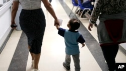 Maria Orbelina Cortez, right, walks with her 3-year-old son, Julio, center, and a worker at the Catholic Charities shelter in McAllen, Texas, Jan. 11, 2019.