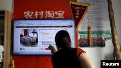 FILE - A customer points at a screen displaying a website of Alibaba's Taobao at a rural service center in Yuzhao Village, Tonglu, Zhejiang province, China, July 20, 2015.