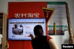 A customer points at a screen displaying a website of Alibaba's Taobao at a rural service center in Yuzhao Village, Tonglu, Zhejiang province, China, July 2015.