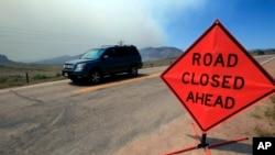 """一辆汽车行驶在科罗拉多州利弗莫尔附近的拉里默郡74号公路西上。路上有""""前方路段关闭""""标示。背后可见野火引起的浓烟。(资料照)"""