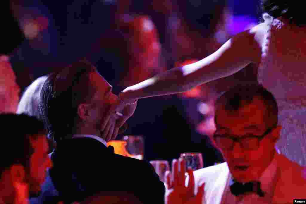 French actress Marion Cotillard touches U.S. actor Leonardo Di Caprio on the cheek during an auction at the amfAR's Cinema Against AIDS 2014 event in Antibes at the 67th Cannes Film Festival in France, May 22, 2014.