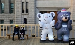 FILE - Children sit next to the 2018 Pyeongchang Winter Olympic Games' official mascots, a white tiger Soohorang, for the Olympics, and black bear Bandabi, right, for the Paralympics, near Seoul Plaza Ice Rink in Seoul, South Korea, Jan. 2, 2018.
