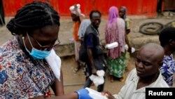 Uma voluntária distribui comida e água a sem-abrigo em Accra, Gana, durante o confinamento obrigatório, devido ao coronavírus