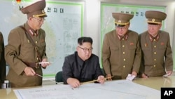 FILE - This image made from video of an Aug. 14, 2017, still image broadcast in a news bulletin, Aug. 15, 2017, by North Korea's KRT shows North Korean leader Kim Jong Un receiving a briefing in Pyongyang.