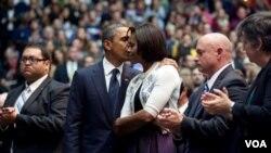A la izquierda, Daniel Hernández aplaude, mientras el presidente Obama abraza a la primera dama Michelle Obama, con el esposo de Giffords, Mark Kelly y la secretaria Janet Napolitano a la dderecha en la foto.