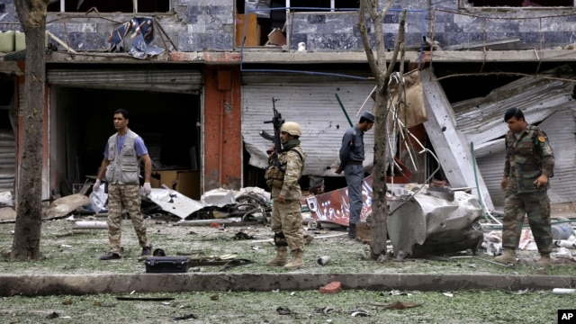 Security personnel investigate the site of a suicide attack that struck the convoy of presidential candidate Abdullah Abdullah in Kabul, June 6, 2014.