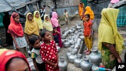 Rohingya women and children wait in a queue to collect water at the Leda camp, an unregistered camp for Rohingya in Teknaf, Bangladesh.