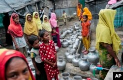 FILE - Rohingya women and children wait in a line to collect water at the Leda camp, an unregistered camp for Rohingya in Teknaf, Bangladesh.