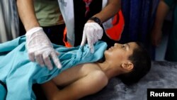 FILE- A boy is treated by medical staff after sustaining injuries from an explosion, at the Shifa hospital in Gaza City, August 8, 2014.