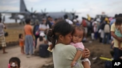 A woman survivor of Typhoon Haiyan weeps as she holds her daughter while waiting for her turn to get on a U.S. Air Force plane to leave for the capital city of Manila, at the airport in Tacloban.