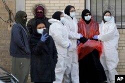 Para pelayat mengenakan pakaian pelindung berkumpul sebelum pemakaman seorang pasien Covid-19, di New York, 22 April 2020.