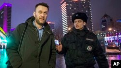 "FILE - Alexei Navalny, shown being detained by a policeman after violating a house arrest order in January, says either state security services or a ""pro-government organization"" was behind the killing of Boris Nemtsov."