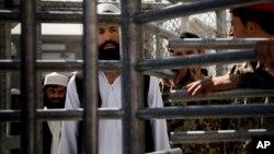 Un prisionero afgano aguarda en fila ser liberado de Parwan luego del traspaso de mando en la cárcel.