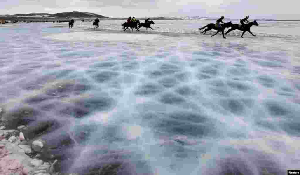 Riders compete on the frozen Yenisei River during the 44th Ice Derby amateur horse race near the settlement of Novosyolovo, some 250 km (155 miles) south of the Siberian city of Krasnoyarsk, Russia.