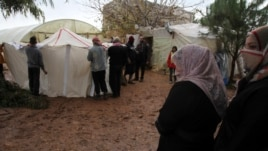 Syrian refugees put up donated new tents after their previous ones where damaged in a storm in Tripoli, Lebanon, Jan. 9, 2013