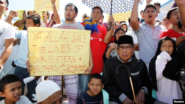 Former Sultan of Sulu Jamalul Kiram III (seated at R) with his followers display placards in front of Blue Mosque in Maharlika village, Taguig city, south of Manila, March 1, 2013