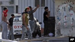 Residents of the Shiite Muslim village of Malkiya, Bahrain, southwest of Manama, watch - some with stones in hand and others photographing riot police and tanks moving in - Sunday, March 20, 2011