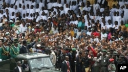 Nigerian President Goodluck Jonathan waves to the crowd during the 50th anniversary celebrations of Nigerian independence, in Abuja, Nigeria, Friday, Oct. 1, 2010.