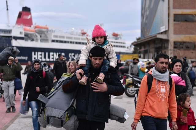 Hundreds of migrants and refugees walk at the port of Piraeus upon their arrival from Lesbos, Feb. 10, 2016. The EU's migration commissioner urged member states to accelerate relocation of refugees from overstretched Greece and Italy.