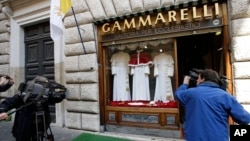 FILE - TV crews film Gammarelli tailoring shop window where three sets of papal outfits - small, medium and large sizes - which will be sent to the Vatican for the new pope, are displayed, in Rome.