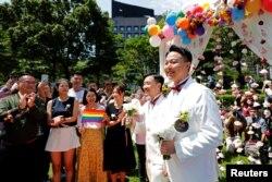 Молодожены празднуют свадьбу после официальной брачной церемонии, Тайбэй, Тайвань, 24 мая 2019 года.